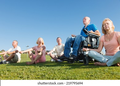 Disabled Man with Group of People practicing yoga outside.