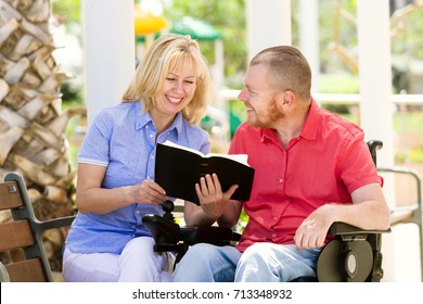Disabled man with his wife having fun reading a book at the park