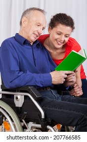 A disabled man and a nurse reading a book together
