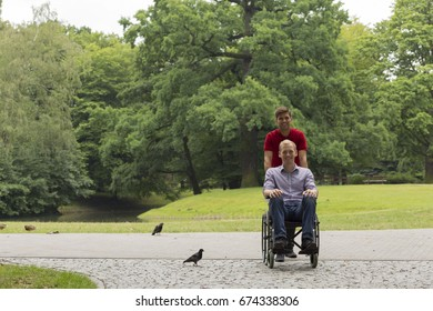 Disabled man on wheelchair during a stroll in the park with his smiling friend