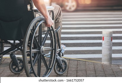 Disabled man on wheelchair preparing to cross the road on pedestrian crossing, copy space.