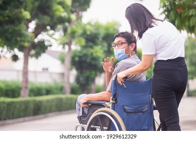 disabled man on wheelchair and sister walking in the park