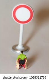 disabled man on a wheelchair standing in front of a no-entry sign in miniature