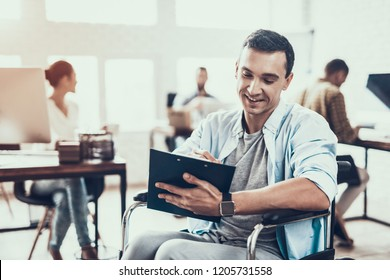 Disabled Man on Wheelchair with Tablet in Office. Teamwork in Office. Young Worker. Sitting Man. Disabled Young Man. Man on Wheelchair. Recovery and Healthcare Concepts. Guy in Office.