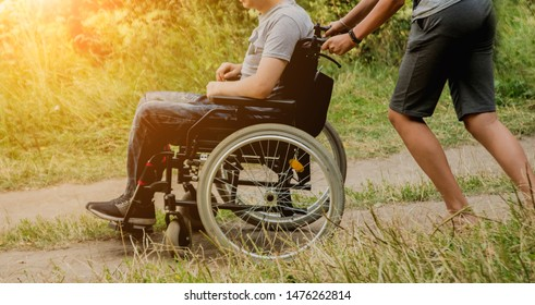 Disabled man resting in a campsite with friends. Wheelchair in the forest on the background of tents. Camping. Summertime