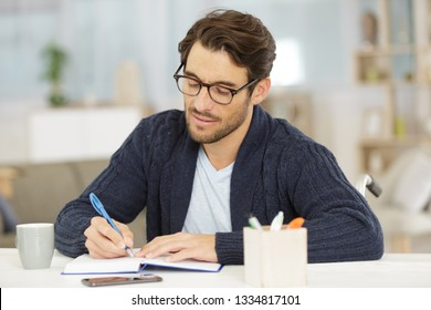 disabled man sat at a table writing in a book