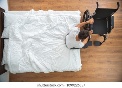 The disabled man sitting on the bed. view from above