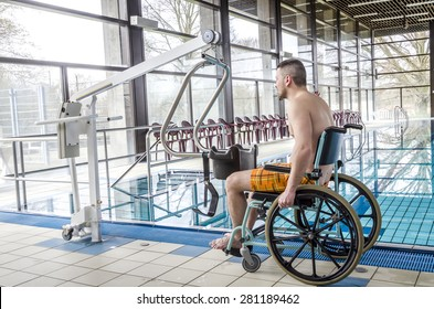 Disabled man in a swimming pool. Wheelchair