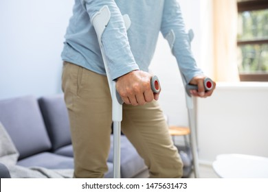 Disabled Man Using Crutches To Walk At Home
