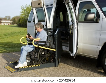 disabled man using the remote control on a wheelchair lift van