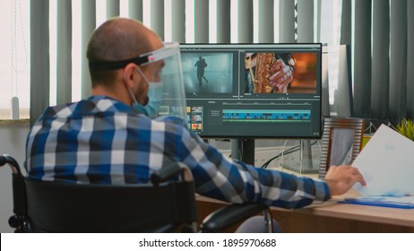 Disabled man videographer with face protection editing video project creating content sitting in wheelchair in new normal office. Blogger working durig global pandemic respecting social distance.