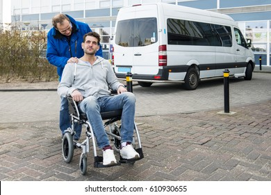 Disabled man in a wheel chair and his male nurse being dropped off at a hospital by a wheel chair taxi