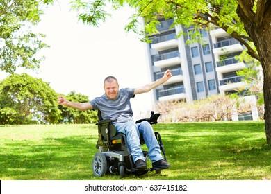 Disabled man in a wheelchair enjoying fresh air at the park