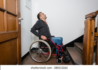 A disabled man in a wheelchair facing a flight of stairs