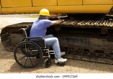 disabled man working on the tracks of a large backhoe