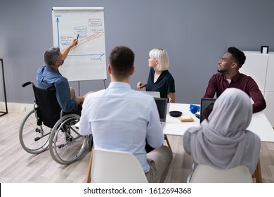 Disabled Mature Businessman Giving Presentation To His Colleagues