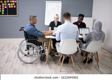 Disabled Mature Businessman Sitting At Desk With Laptop In Conference Room