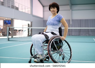 Disabled mature woman on wheelchair on tennis court.