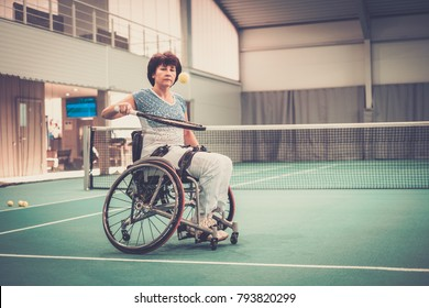 Disabled mature woman in wheelchair on a tennis court.