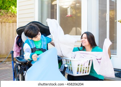 Disabled nine year old boy in wheelchair helping teen sister fold laundry outside on patio