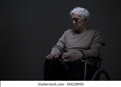 Disabled old man sitting on a wheelchair in empty room