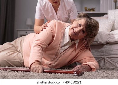 Disabled older woman on floor and caring young assistant