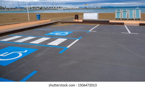 Disabled parking divided by a pedestrian crossing on the beach and blue sea background. Empty convenient parking for cars with places for disabled people. Parking on the beach. Marking on asphalt road