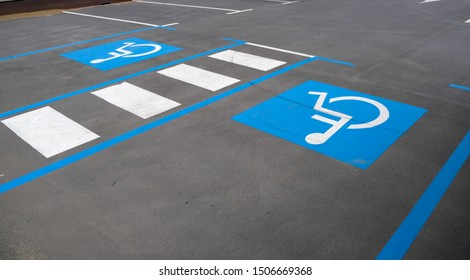 Disabled parking divided by a pedestrian crossing. Empty convenient parking for cars with places for disabled people. Marking on asphalt road.