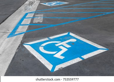 Disabled parking icon painted on pavement. Blue and white wheelchair symbol.