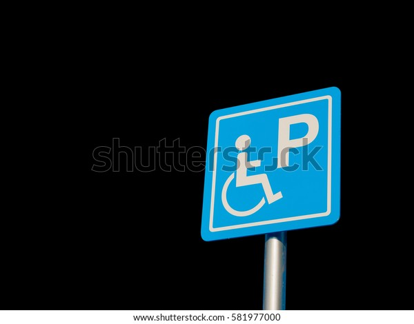 Disabled parking space and wheelchair way sign and symbols on a pole warning motorists isolate on Black background