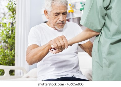 Disabled Patient Holding Hand Of Nurse In Rehab Center