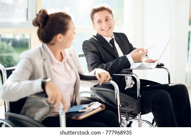 Disabled people in business clothes. A girl and a man in a wheelchair in a bright waiting room. Businessmen with disabilities.