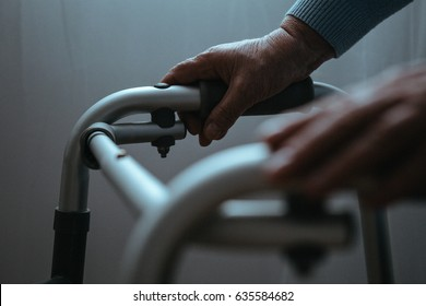 Disabled person holding hands on walker, close up