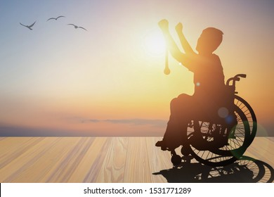 Disabled person silhouette winners hand holding gold medal top of wheelchair have sunset with mountain background. International Disability Day or Handicapped Paralympics. Challenge, Conquer concept.