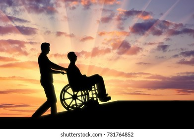 Disabled person in a wheelchair and the man helps him climb up the ramp. Concept of caring for the disabled in moving around the city