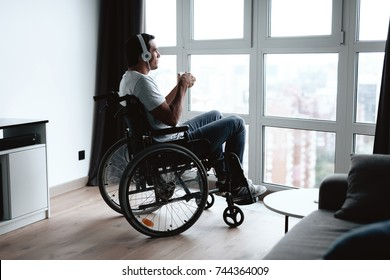 A disabled person in a wheelchair sits in front of a large panoramic window and listens to music on the smartphone. He has a smartphone in his hands and headphones on his head.