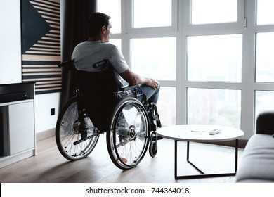 The disabled person in a wheelchair sits in front of a large panoramic window and looks into it. He is sad. He is in the living room of his modern apartment.