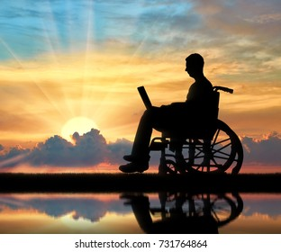 A disabled person in a wheelchair working with a laptop in hand near the river with his reflection. The concept of the opportunity to work for people with disabilities