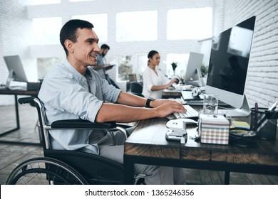 Behinderte im Rollstuhl arbeiten im Büro am Computer. Er lächelt und leidenschaftlich an den Workflow. Büroangestellte arbeiten zusammen.