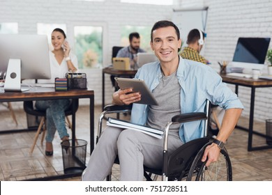 Disabled person in the wheelchair works in the office. In his hands is a tablet. He is posing for the camera. Man is smiling. His colleagues work nearby.