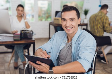 Disabled person in the wheelchair works in the office. He writes in a tablet for papers. Man is smiling. His colleagues work nearby.