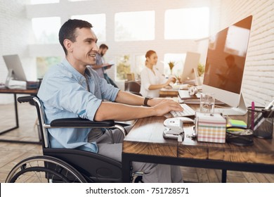 Disabled person in the wheelchair works in the office at the computer. He is smiling and passionate about the workflow.