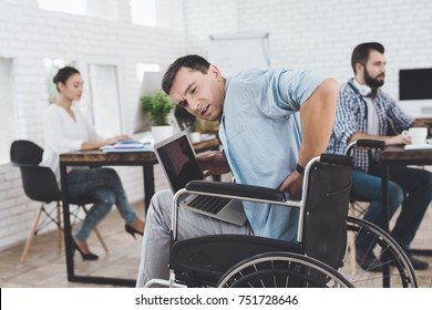 Disabled person in the wheelchair works in the office on laptop. He feels pain and fatigue in his back. His colleagues work nearby.