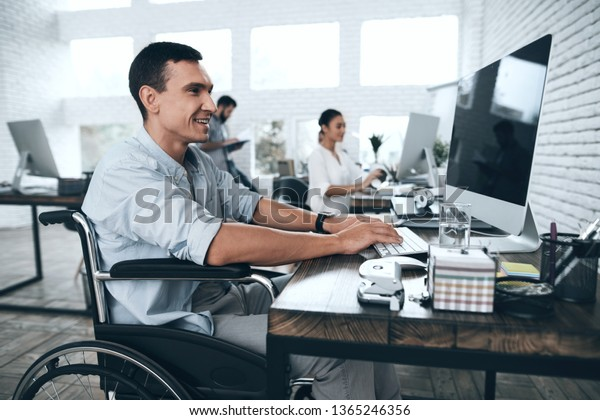 Disabled person in the wheelchair works in the office at the computer. He is smiling and passionate about the workflow. Office people working together.
