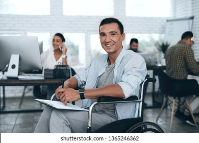Disabled person in the wheelchair writes in a tablet for papers . Work and rest life in office with good workers.