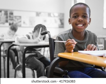 Disabled pupil smiling at camera in classroom at the elementary school