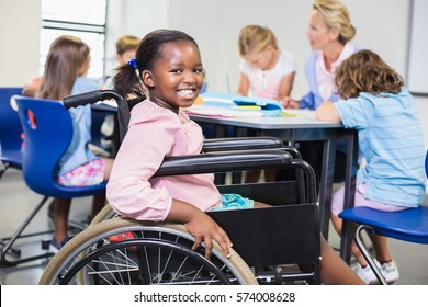 Disabled schoolgirl smiling in classroom at school