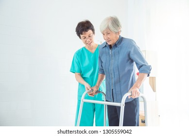 Disabled senior asian woman walking with assistance from nurse in hospital