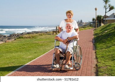 Disabled senior man being pushed by his loving wife at beach on sunny day