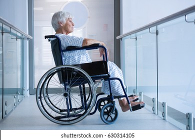 Disabled senior patient on wheelchair in hospital passageway at hospital